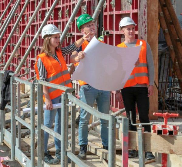 Auszubildende mit Bauplan auf Baustelle